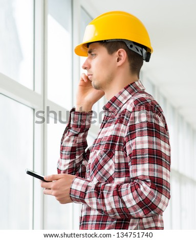 engineer in a helmet uses a digital tablet - stock photo