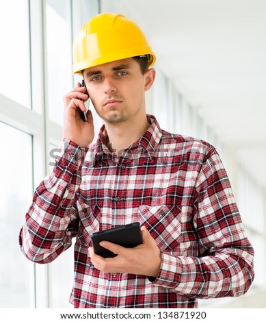 engineer in a helmet uses a smart phone and digital tablet - stock photo