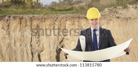 engineer in a helmet with paper plans of buildings in the trench at the site of the future foundation - stock photo
