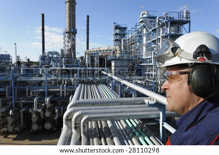 engineer in close-ups standing in front of large oil and gas refinery - stock photo