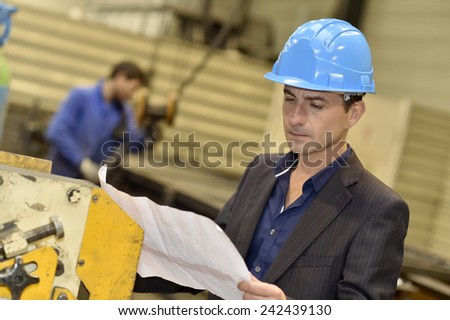 Engineer in factory reading blueprint