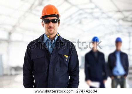 Engineer in front of his team. Bright background - stock photo