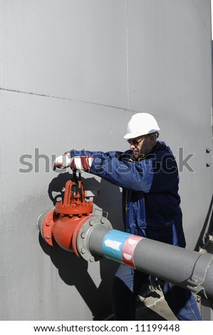 engineer in hard-hat working on pipeline pump inside oil industry - stock photo