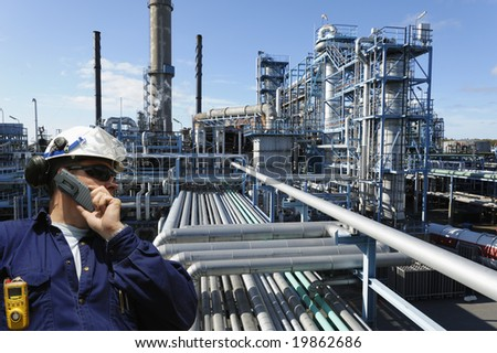 engineer in hardhat talking in phone, large oil and fuel refinery in background - stock photo