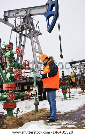 Engineer in orange uniform and helmet on of background the pump jack. - stock photo