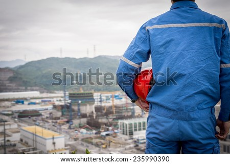 engineer in safety suit stand in front of nuclear construction - stock photo
