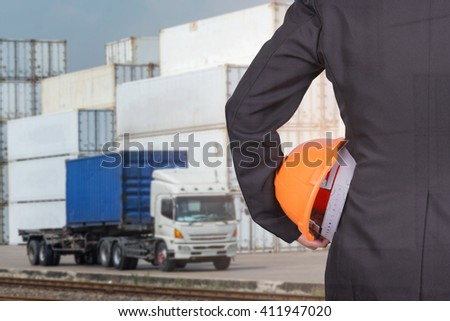 engineer in suit holding helmet and truck and container in cargo - stock photo