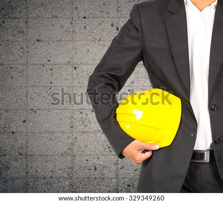 engineer in suit holding yellow helmet for workers security on granite wall background, industrial concept - stock photo