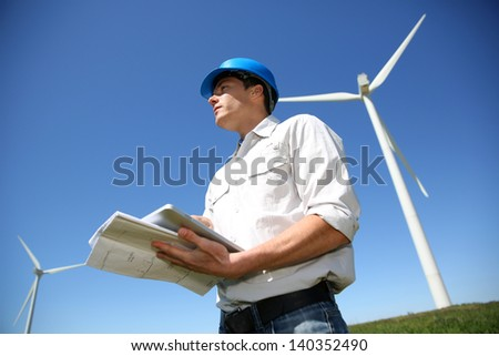 Engineer in wheat field checking on turbine production - stock photo