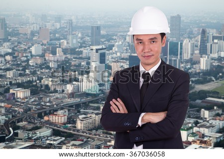 engineer in white helmet with arms crossed, city background - stock photo