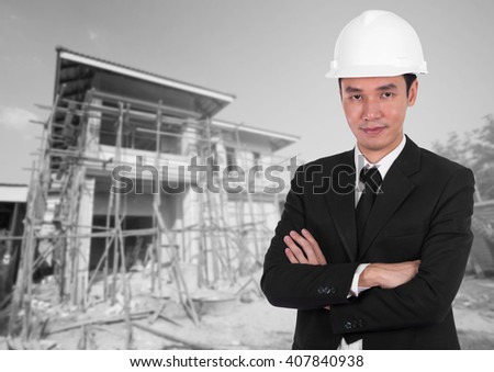 engineer in white helmet with arms crossed, house construction background - stock photo
