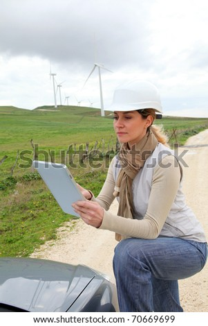 Engineer in wind turbines field using electronic tablet - stock photo