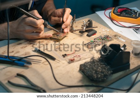 Engineer is making electronic board on his wooden table - stock photo