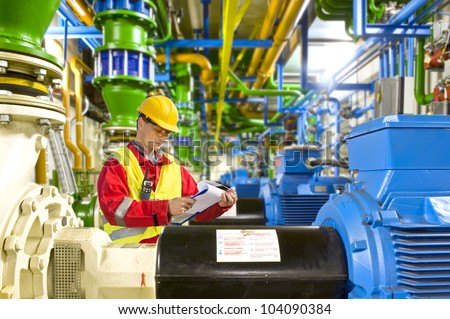 Engineer looking at a checklist during maintenance work in a large industrial engine room - stock photo