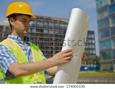 Engineer looking at blueprint on construction site - stock photo