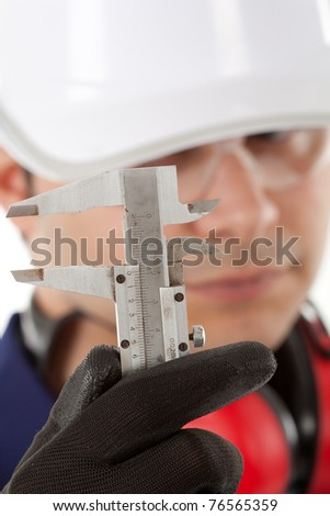 Engineer looking closely at a gauge - stock photo