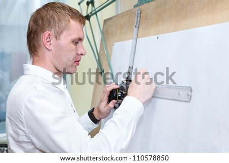 Engineer making construction project by pencil on drawing board