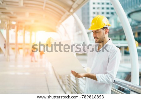 Engineer man wearing safety helmet hold imagen de archivo stock engineer man wearing safety helmet and hold blueprint document at construction site concept of work malvernweather Image collections