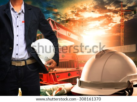 engineer man with white safety helmet standing against working table and building construction scene  - stock photo