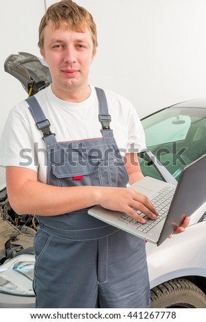 engineer of mechanics with a laptop near a car in a garage - stock photo