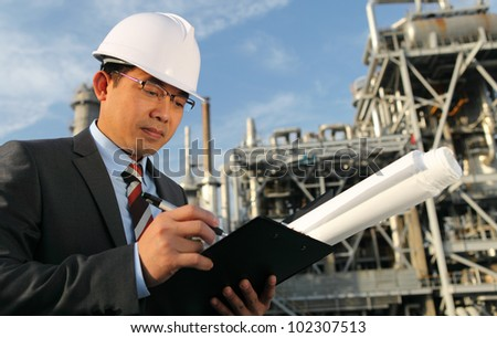 engineer oil industry write on noteboard with large industry background