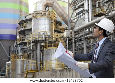 engineer oil refinery with blueprint on location site - stock photo