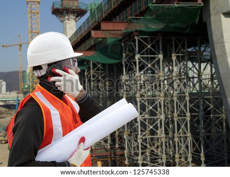 Engineer on construction site using mobile cellphone - stock photo