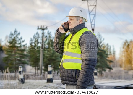 Engineer on railway crossing with a smartphone