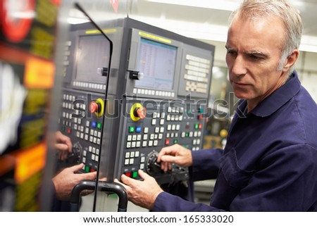 Engineer Operating Computer Controlled Lathe - stock photo