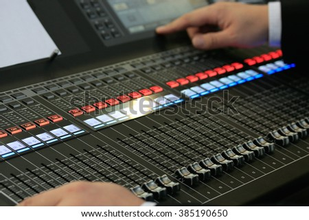 Engineer operating the controls of sound mixing board. Close up view. Selective focus. - stock photo
