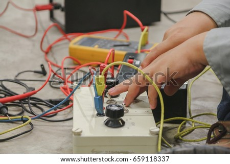 Engineer or Technician use test box for inject voltage into equipment which checking voltage by digital multimeter. Selective focus