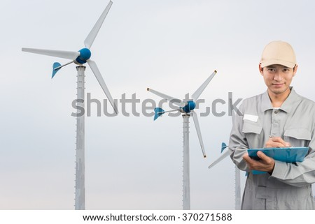 Engineer or technician write book with large Wind Turbine Power Station background