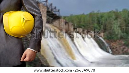engineer or worker hand hold yellow helmet for workers security over Background to dam bridge weir in perspective Idea of power energy electricity Empty Copy space for inscription - stock photo
