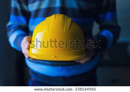 engineer or worker hand holding yellow helmet  Idea oe concept of safety - stock photo