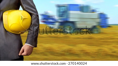 engineer or worker hold in hand yellow helmet for workers security against combine harvester on autumn wheat field with a blue cloudy sky nature background Empty space for inscription - stock photo