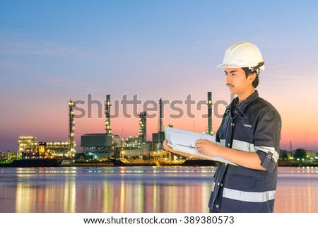 Engineer over Oil refinery among the river background.