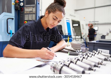 Engineer Planning Project With CNC Machinery In Background