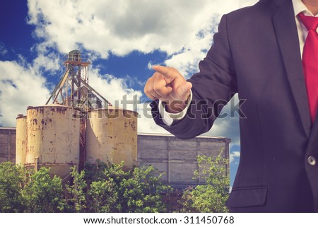 engineer pushing on a touch screen interface working at high building construction site against blue sky with in concept ecology and real estate vintage color - stock photo