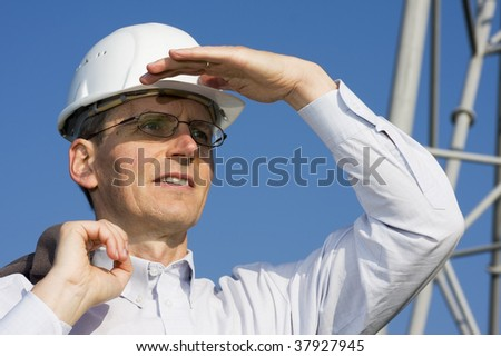 Engineer searching in front of steel construction - stock photo