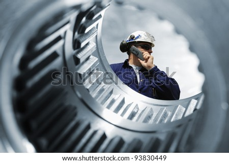 engineer, seen through the shaft of giant gear wheel, machine engineering idea - stock photo