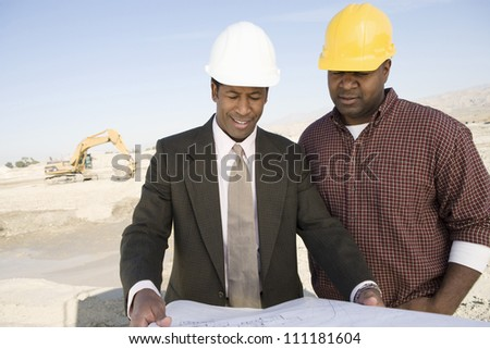 Engineer showing blueprint  for a worker - stock photo