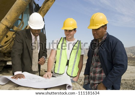 Engineer showing blueprint to workers - stock photo