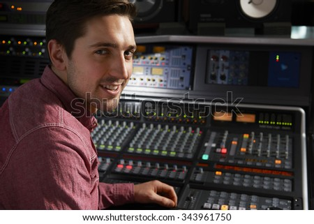 Engineer Sitting At Mixing Desk In Recording Studio - stock photo