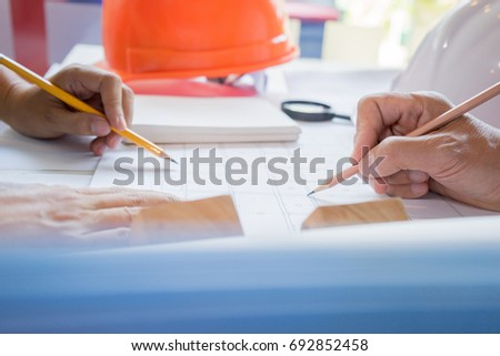 Engineer sketching architectural project on blueprint, engineering concept, architectural concept