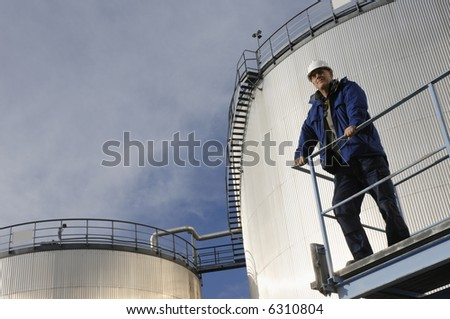 engineer standing in front of oil-storage-tanks, tilted perspective - stock photo
