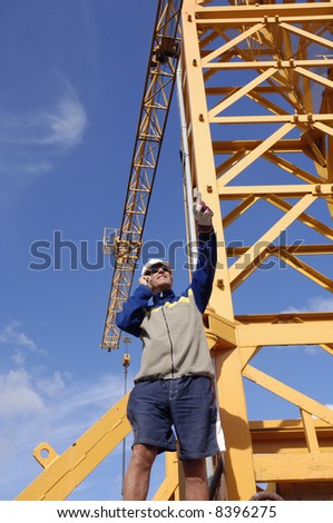 engineer standing on crane directing crane-driver, blue sky.