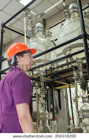 Engineer student looking part of machine in laboratory - stock photo