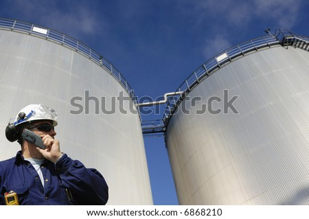 engineer talking in mobile-phone in front of refinery oil storage tanks - stock photo