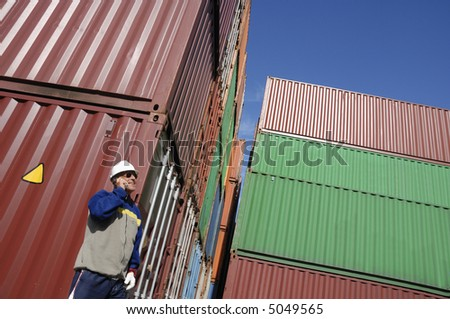 engineer talking in mobile-phone with stacks of freight containers in background - stock photo