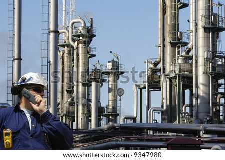 engineer talking in phone in front of large oil and gas refinery - stock photo